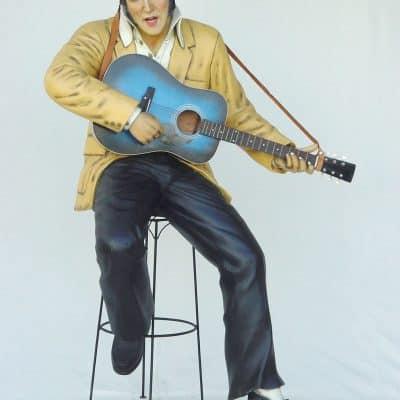 פסל של אלביס יושב ומנגן גיטרה